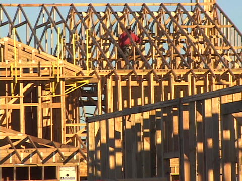 A construction worker works on the framework of a new building Live Action