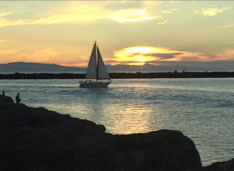 A sail-boat drifts gently along the water as a man fishes... Stock Video Footage