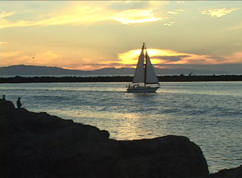 A sail-boat drifts gently along the water as a man fishes on the shore during golden-hour Footage