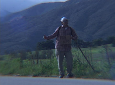 A hiker attempts to hitch a ride in a rural area during... Stock Video Footage