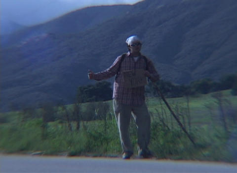 A hiker attempts to hitch a ride in a rural area during golden-hour Footage