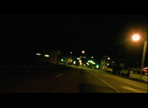 Traffic travels through a city at night Stock Video Footage