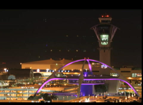Airplanes fly past an airport control tower at night Stock Video Footage