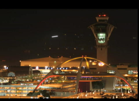 Airplanes fly past an airport control tower at night Footage
