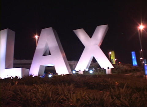 Spotlights illuminate the giant letters LAX at the entrance of Los Angeles International airport Footage