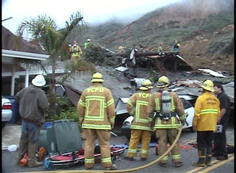 Firefighters examine a house that has been destroyed Stock Video Footage