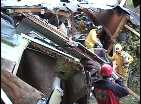 Firefighters dig through a house that has fallen on a car Footage