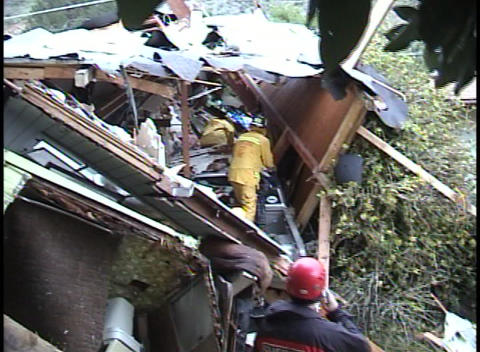 Firefighters dig through a house that has fallen on a car Stock Video Footage