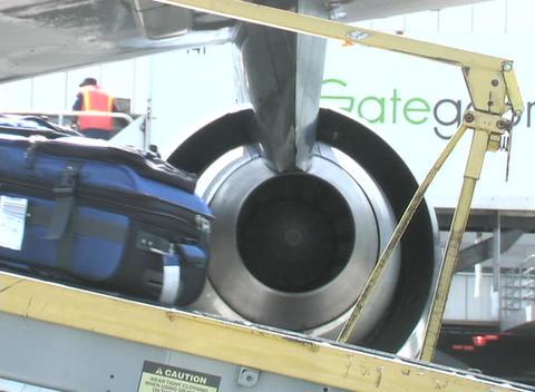 An airline employee unloads cargo from a conveyor belt Stock Video Footage