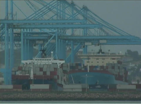Machines work to unload supplies at a container port Stock Video Footage