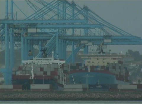 Machines work to unload supplies at a container port Footage