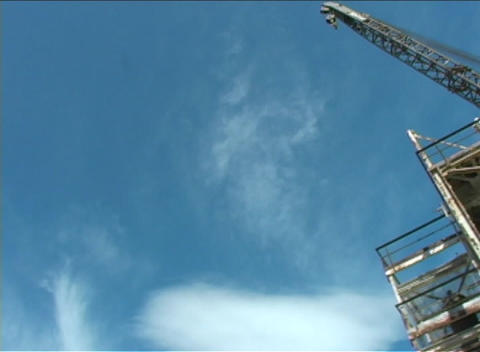 A large crane stands at the top of a large metal structure Stock Video Footage
