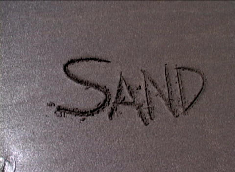 The word sand is carved in the sand and then washed away... Stock Video Footage
