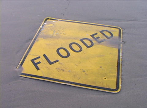 A street-sign that reads FLOODED is covered in mud as... Stock Video Footage