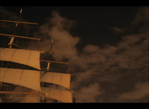 An accelerated shot of clouds flowing past the masts of an old-time sailing ship at night Footage
