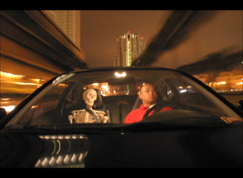 An accelerated shot of a car driving through city streets with two passengers, a skeleton and a man Footage