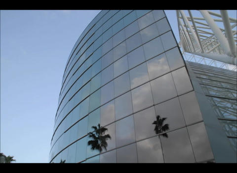 A shiny contemporary building reflects fast moving clouds in a blue sky Footage