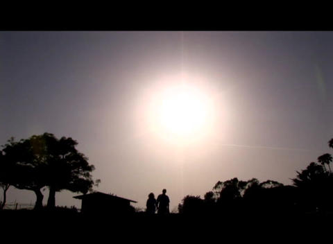 Medium shot of a couple walking hand-in-hand silhouetted... Stock Video Footage