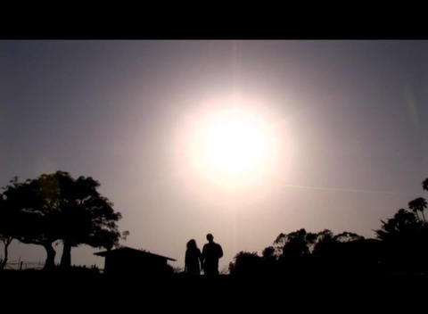 Medium shot of a couple walking hand-in-hand silhouetted by the sun Footage