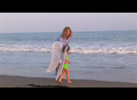 Medium shot of a mom and daughter playing on the beach Stock Video Footage