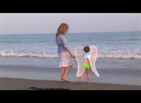 Medium shot of a mom and daughter playing on the beach Footage
