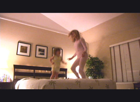 Medium shot of a mother and daughter jump on a bed Stock Video Footage