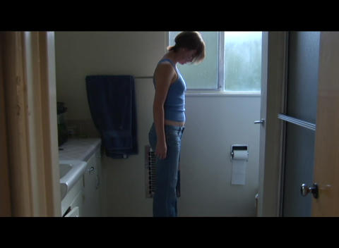 Pan-down as a woman weighs herself in the bathroom Footage