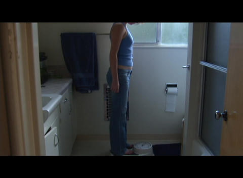 Pan-down as a woman weighs herself in the bathroom Stock Video Footage