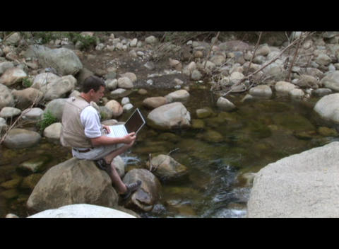 Medium shot of a man working on a laptop computer near a... Stock Video Footage