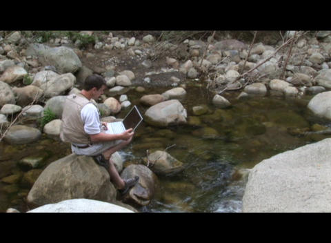 Medium shot of a man working on a laptop computer near a stream Footage