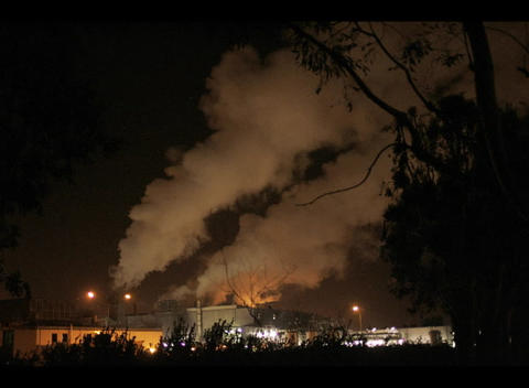 A time-lapse medium shot of smoke billowing from a factory at night Footage