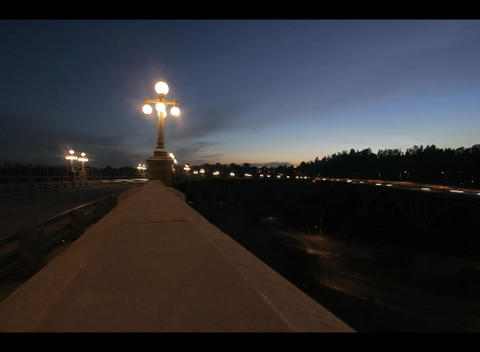 A time-lapse shot of a freeway median, street-lights, and traffic at golden hour Footage