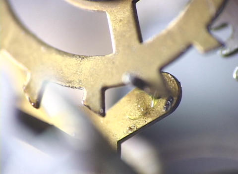 Rotating teeth on a wheel gear move a lever in this close-up Stock Video Footage