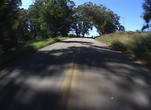 Point-of-view shot traveling down a narrow highway with shadows from trees Footage