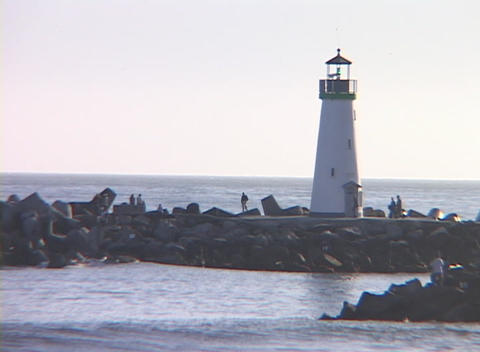 Medium shot of a lighthouse with people observing the... Stock Video Footage