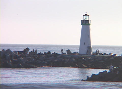 Medium shot of a lighthouse with people observing the water and a gull swooping towards the surf Footage