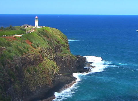 A lighthouse stands guard on top of a rocky cliff as a... Stock Video Footage