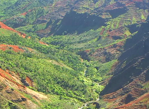 Camera zooms out on volcanic region where a stream and new roads both cut through the bright green v Footage