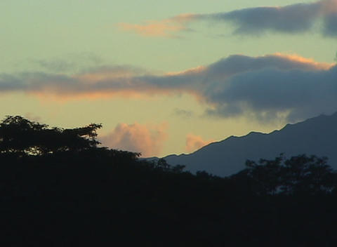 Sky above silhouetted mountains is filled with clouds of many hues Footage