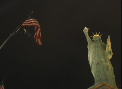 Low-angle shot of the Statue of Liberty, and US flag in front of the New York, New York Hotel and Ca Footage