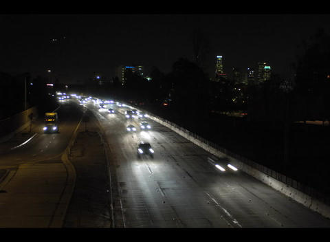 Traffic speeds along a busy freeway at night in this... Stock Video Footage