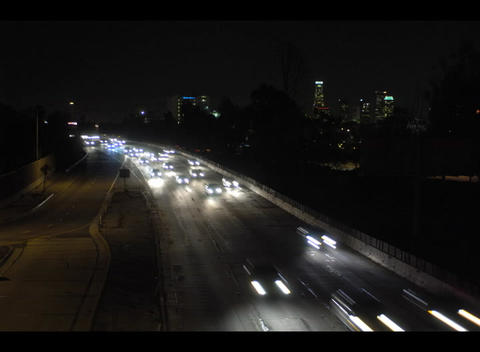 Traffic speeds along a busy freeway at night in this accelerated shot Footage