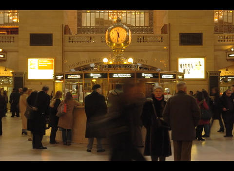 People purchase tickets, and mill around a train stations ticket booth in this accelerated shot Footage