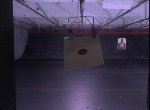 A target at an indoor shooting range recedes toward a far... Stock Video Footage