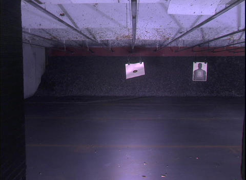A target at an indoor shooting range recedes toward a far... Stock Video Footage