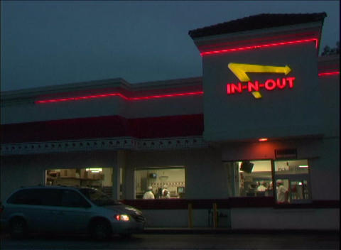 Patrons pick up food at the busy In-and-Out drive through restaurant Footage