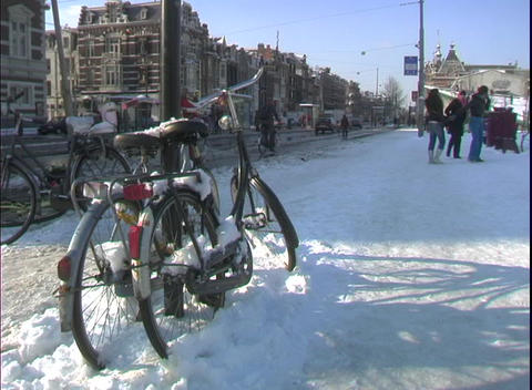 bicycles sit in the snow on an Amsterdam street Stock Video Footage