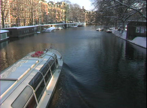 A water taxi travels through a canal in Amsterdam Footage