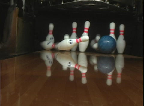 A blue bowling ball rolls down the lane for a strike Live Action