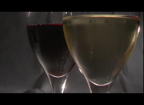Red and white wine fill two wine glasses Footage